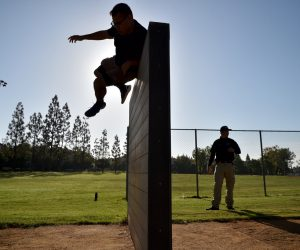 Applicants make their way over a six-foot wall during Tustin PD's Physical Agility Test at Tustin Sports Park. Photo by Steven Georges/Behind the Badge