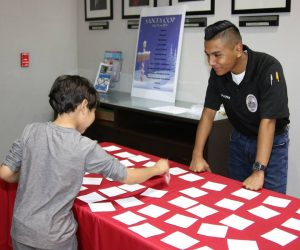 Explorer working at a game table during 2019 Santa Cop event