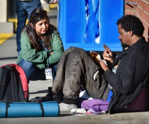 Milena Andreani of the Orange County Health Care Agency ties to talk to a homeless man into getting the help he needs during an outreach outing while partnering with the Tustin PD. Photo by Steven Georges/Behind the Badge OC